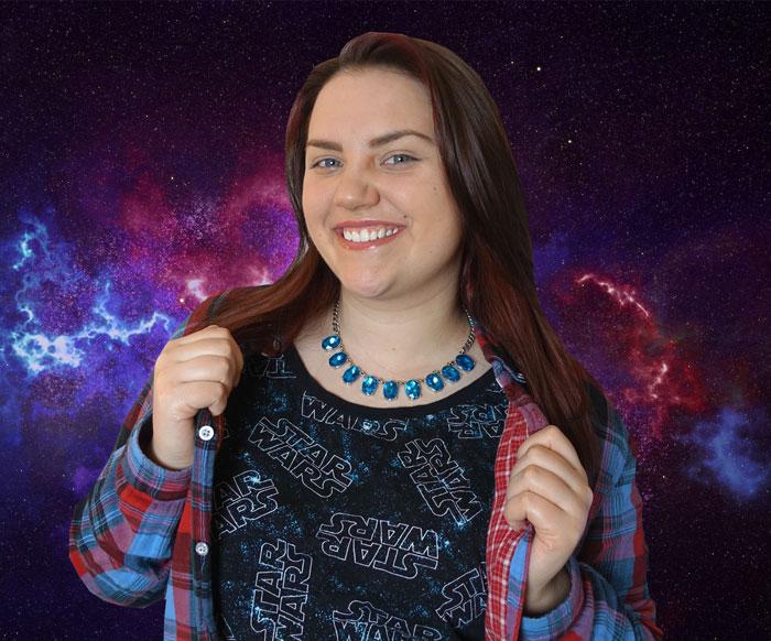 Kimmy POWER har en Star Wars-tröja på sig och ler stort. Bakgrunden föreställer lila rymd.