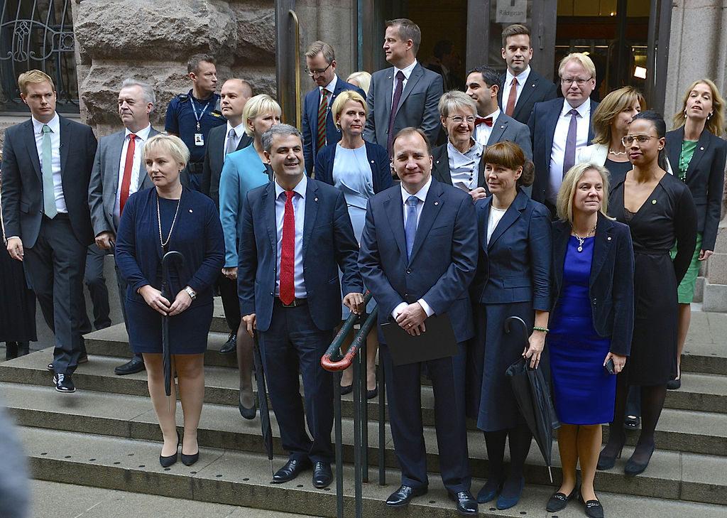 En grupp av människor står på en trappa. Kvinnorna har fina kjolar och kavajer, och männen har slips och kostym. Stefan Löfven har en mörkblå kostym och brunt tunt hår.