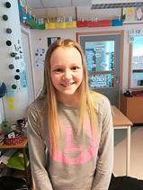 Linnea står i ett klassrum. Hon har en grå tröja med rosa tryck och långt blont hår som hänger ner över hennes axlar. Hon ler stort mot kameran.