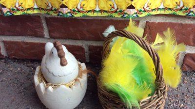 Påskpynt: en korg med gula och gröna fjädrar, en porslinshöna på ett halvt porslinsägg, en pappersdekor med gula kycklingar.
