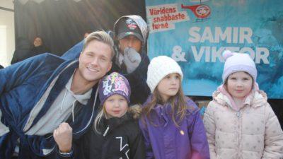 Artisterna Samir och Viktor ler mot kameran tillsammans med tre barn framför en plansch det står Samir & Viktor på.