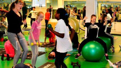Tre barn och en vuxen tränar styrka på ett gym.