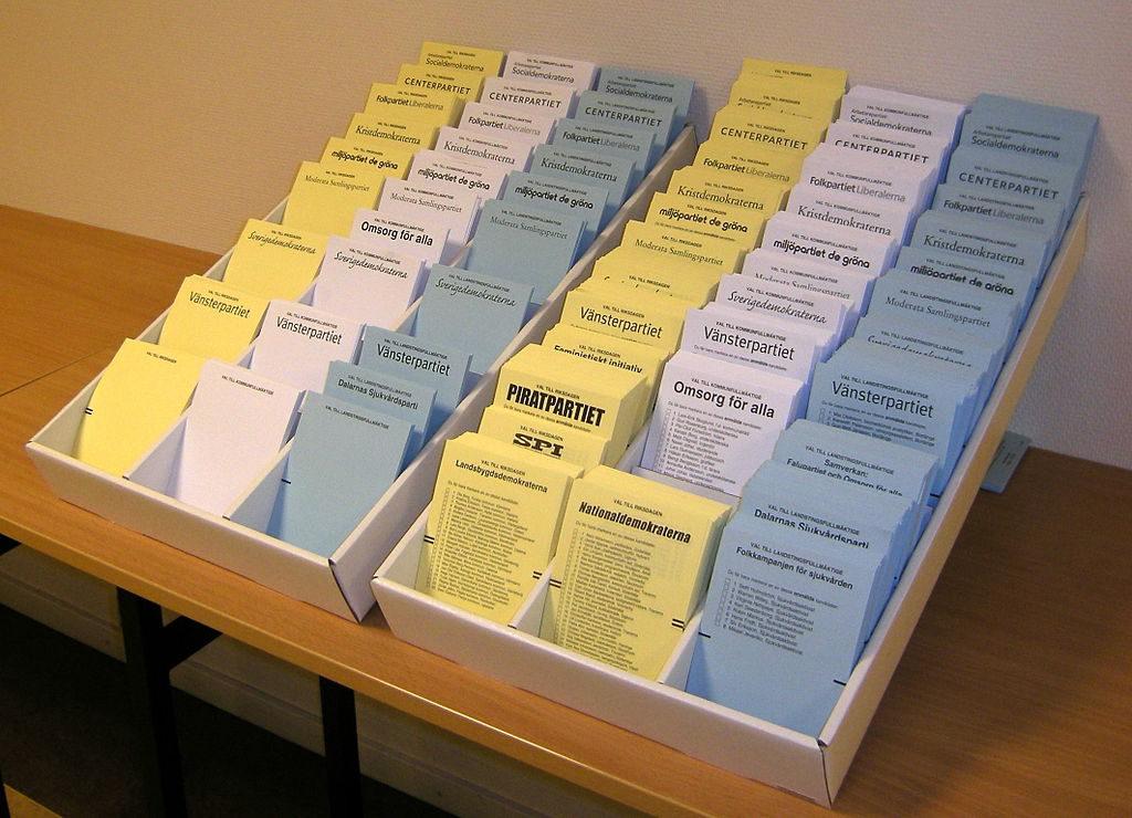 Gula, vita och blåa lappar står i en låda. På lapparna står ett partinamn högst upp och nedanför är en lista.