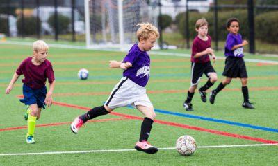 Barn som spelar fotboll utomhus
