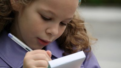 En flicka skriver i ett block. Hon har lockigt blont hår och en lila jacka.