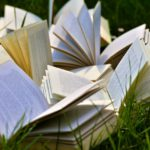 Uppslagna böcker på en gräsmatta