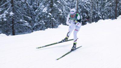 Charlotte åker skidor fort fram genom en snötäckt skog. Hon har färgglada skidor och vita tajta kläder. Hon har mössa, gula glasögon och håller stavarna under armarna så de pekar bakåt.
