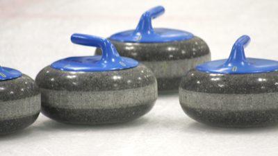 Grå curlingstenar med blå handtag som ligger på is