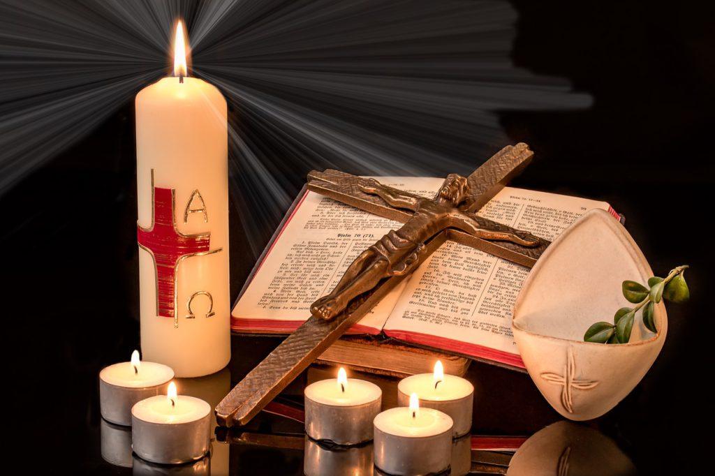 En bibel ligger uppslagen. På bibeln ligger ett kort med Jesus på. Bredvid står ett stort ljus med ett rött kors på. Runtomkring står flera små ljus.