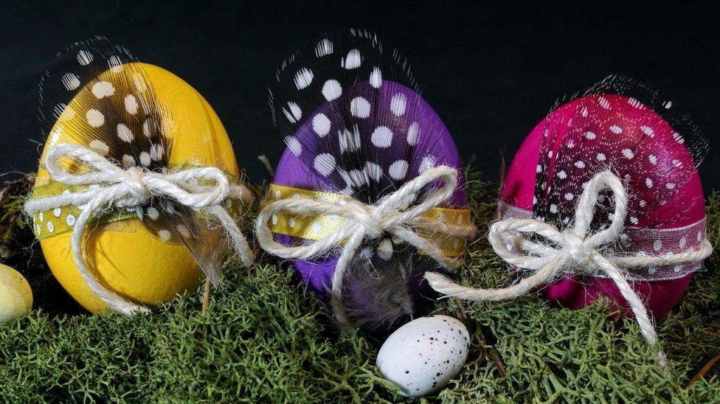 Tre färgglada ägg står i mossa. Ägen har fina barn och fjädrar knutna runt sig.
