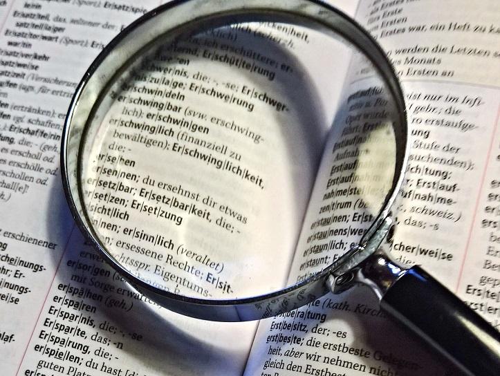 Ett förstoringsglas som ligger på en bok en uppslagen bok.