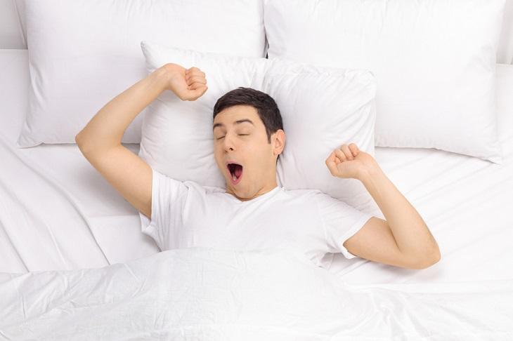 En person ligger i en vit säng. Han gäspar och sträcker på armarna.