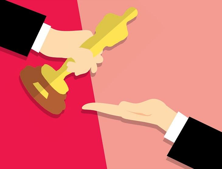 En tecknad bild på två armar med svarta kostymer. Den ena handen ger en oscarsstatyett till den andra handen. Statyetten är formad som en gubbe och är gjord av guld.