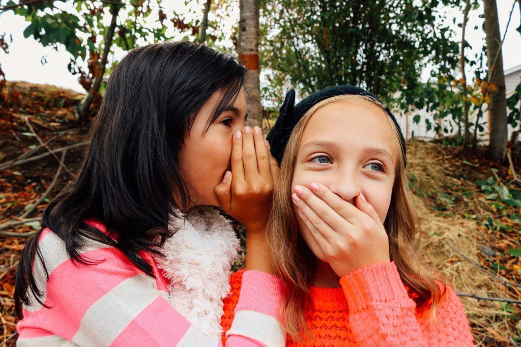 Två tjejer sitter bredvid varandra utomhus. Den ena tjejen har mörkt hår och viskar nåt i den andras öra. Hon har ljust hår och håller för munnen.