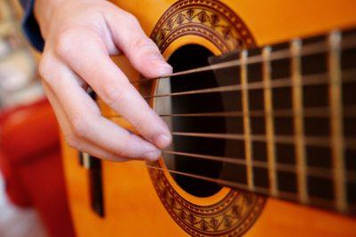 En hand på gitarrsträngar