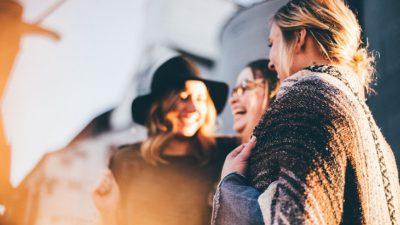 En suddig bild på tre kvionnor som står tillsammans. De skrattar och ser glada ut.
