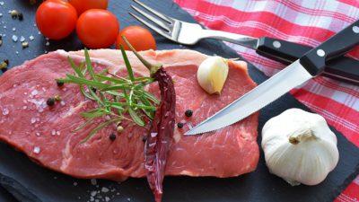 En rå köttbit ligger på en skärbräda. På köttbiten ligger en kryddkvist och en torkad chili. Bredvid köttebiten ligger en kniv, en vitlök och några tomater. Det är strött peppar och salt över köttbiten och skärbrädan.