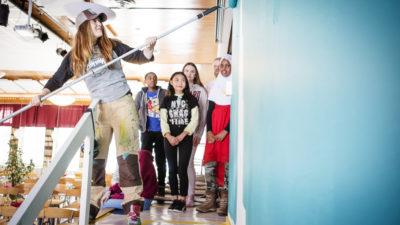 En konstnär målar en vägg turkos. Fyra barn står och tittar på.