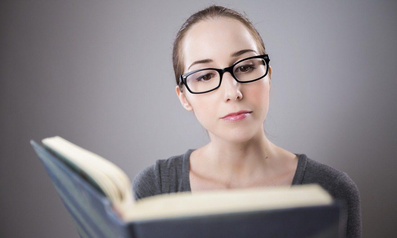 En kvinna med glasögon. Hon tittar i en bok.
