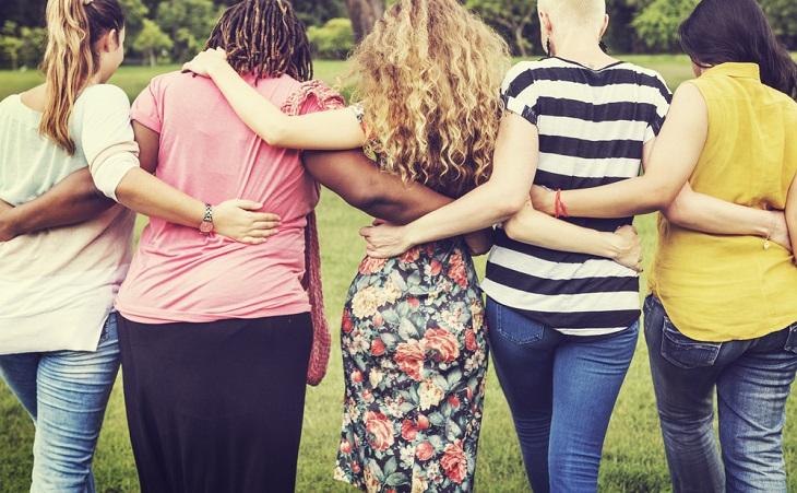 Flera kvinnor syns bakifrån. De går i rad och håller om varandras ryggar. Någon har jeans, någon annan har klänning. Nåon har kort hår, en annan har rastaflätor-