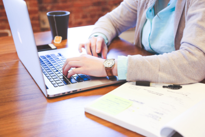 En person som sitter med en laptop vid ett träbord.