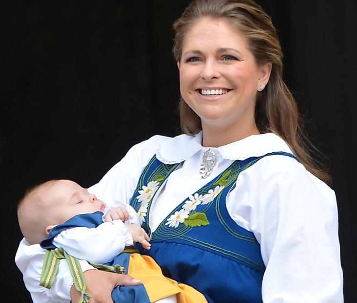 Prinsessan Madeleine har svensk folkdräkt på sig som är gul och blå. Hon ler stort och håller en bebis i sina armar.