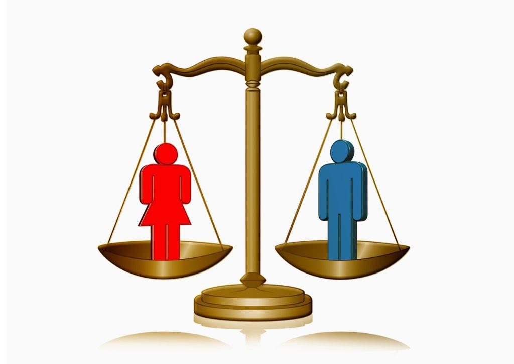 En vågskål. Ena skålen har en blå gubbe i sig, den andra har en röd gubbe med kjol.