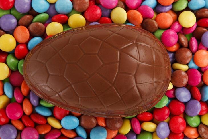 Ett stort chokladägg ligger på en bädd av färgglada chokladlinser.