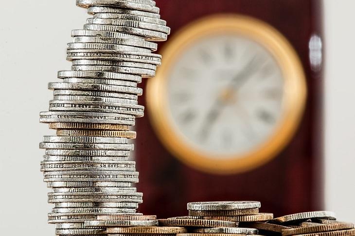 När bild på mynt som är staplade i en hög. I bakgrunden syns en suddig klocka.