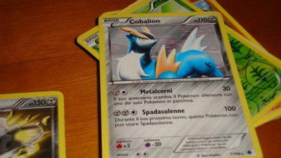 Några pokemonkort ligger i en hög på ett bord. Det översta kortet har gul kant och grå bakgrund. Längst upp är en bild på en blå pokémon med horn. På nedre delen av kortet står text och olika symboler.