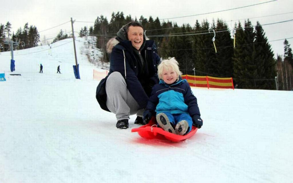 Ett barn sitter på en röd pulka i snötäckt backe. Bakom barnet sitter en vuxen på huk och skrattar.
