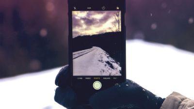 En person håller en mobil i ett snötäckt landskap