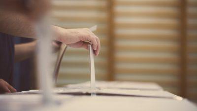 Flera lådor står i rad. Varje låda har en springa på ovansidan. En hand stoppar ner en lapp i springan i en av lådorna.