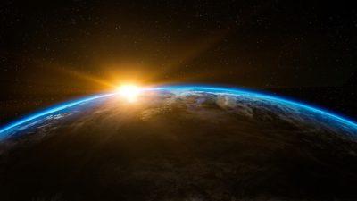 Jorden från rymden. Jorden skapar en böjd horisont där solen stiger upp bakom.