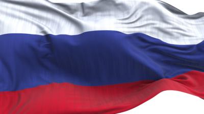 En rysk flagga som vajar i vinden. Den har tre ränder på längden, den översta är vit, den i mitten är blå, och den längst ner är röd.