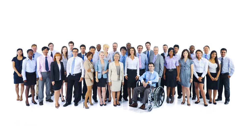 En grupp med både kvinnor och män, med olika hudfärg står tillsammans. Alla har ganska fina jobbkläder, som slips och kjol. I mitten sitter en person i rullstol.