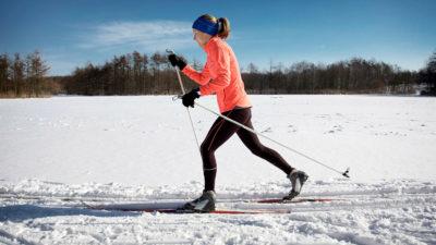 Motionsklädd skidåkare glider fram genom snö under klarblå himmel.