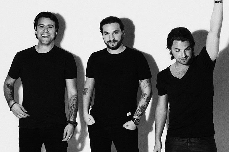 Swedish House Mafia står framför en vit vägg. De står bredvid varandra och har svarta t-shirts på sig. En skrattar, en ler lite försiktigt och en tittar bort och sträcker upp sin arm i luften.