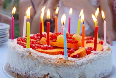 En tårta dekorerad med frukter och färgglada ljus