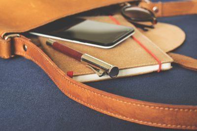 En brun läderväska som ligger på en blå matta. Ur väskans öppning sticker det fram ett par solglasögon, ett anteckningsblock. en mobiltelefon och en penna.