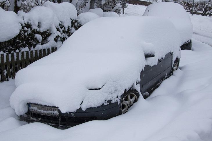 En bil står intill ett staket. Bilen är helt översnöad. Det syns bara däcken och en bit längst ner på bilen.