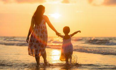 En kvinna och ett barn syns bakifrån. I bakgrunden syns vatten och en solnedgång.
