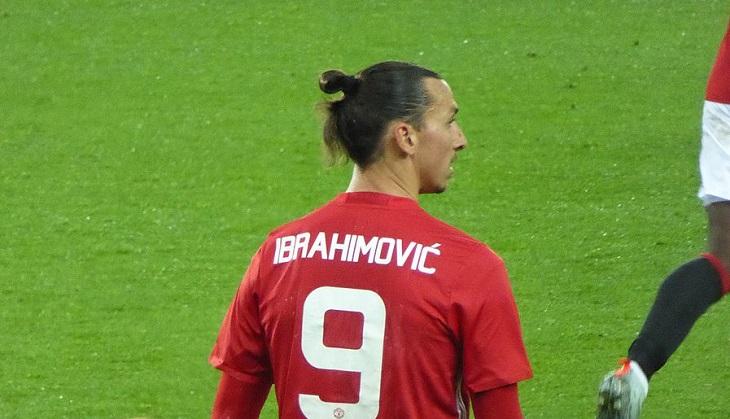 Zlatan står på en fotbollsplan med ryggen mot oss. Han tittar åt sidan och har en röd fotbollströja på sig. På ryggen står det Ibrahimovic och siffran 9 i vitt.