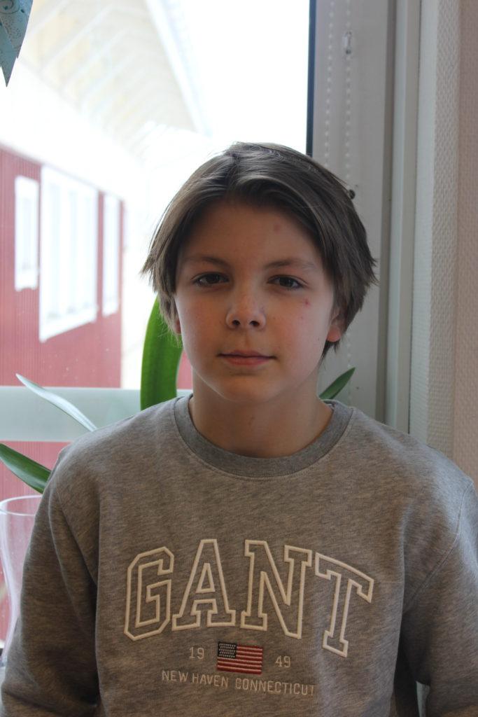 Adam står framför ett fönster. Han har en grå tröja och halvlångt hår med en mittbena.