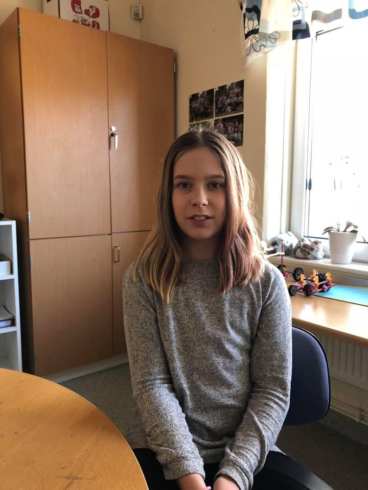 Ella sitter på en kontorsstol med ett bord framför sig. I bakgrunden är det ett fönster och ett stort skåp. Ella har en långärmad tröja och hår som går ner till axlarna med en mittbena.