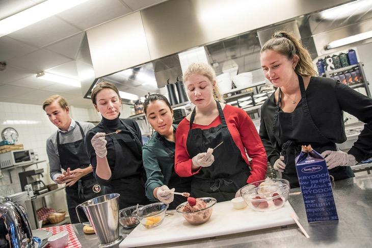 Fem elever står i ett skolkök och smakar på olika glassar.