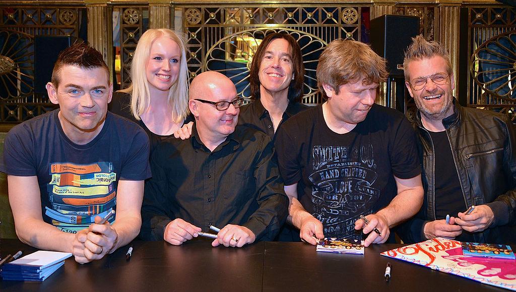 Bandet sitter vid ett svart bord. De är alla medelålders och har svarta kläder.