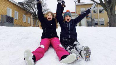 Två barn sitter i en snöig backe på en skolgård.