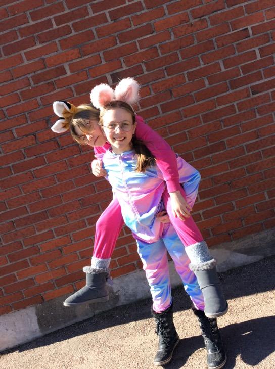 Ett barn på ryggen på ett annat barn. Barnen har kaninöron på sig och färgglada kläder.