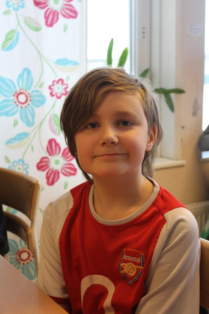 Emil sitter vid en skolbänk. Han har halvlångt brunt hår och en röd fotbollströja.